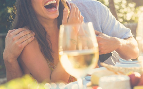 Couple Laughing and Enjoying Romantic Meal with Friends
