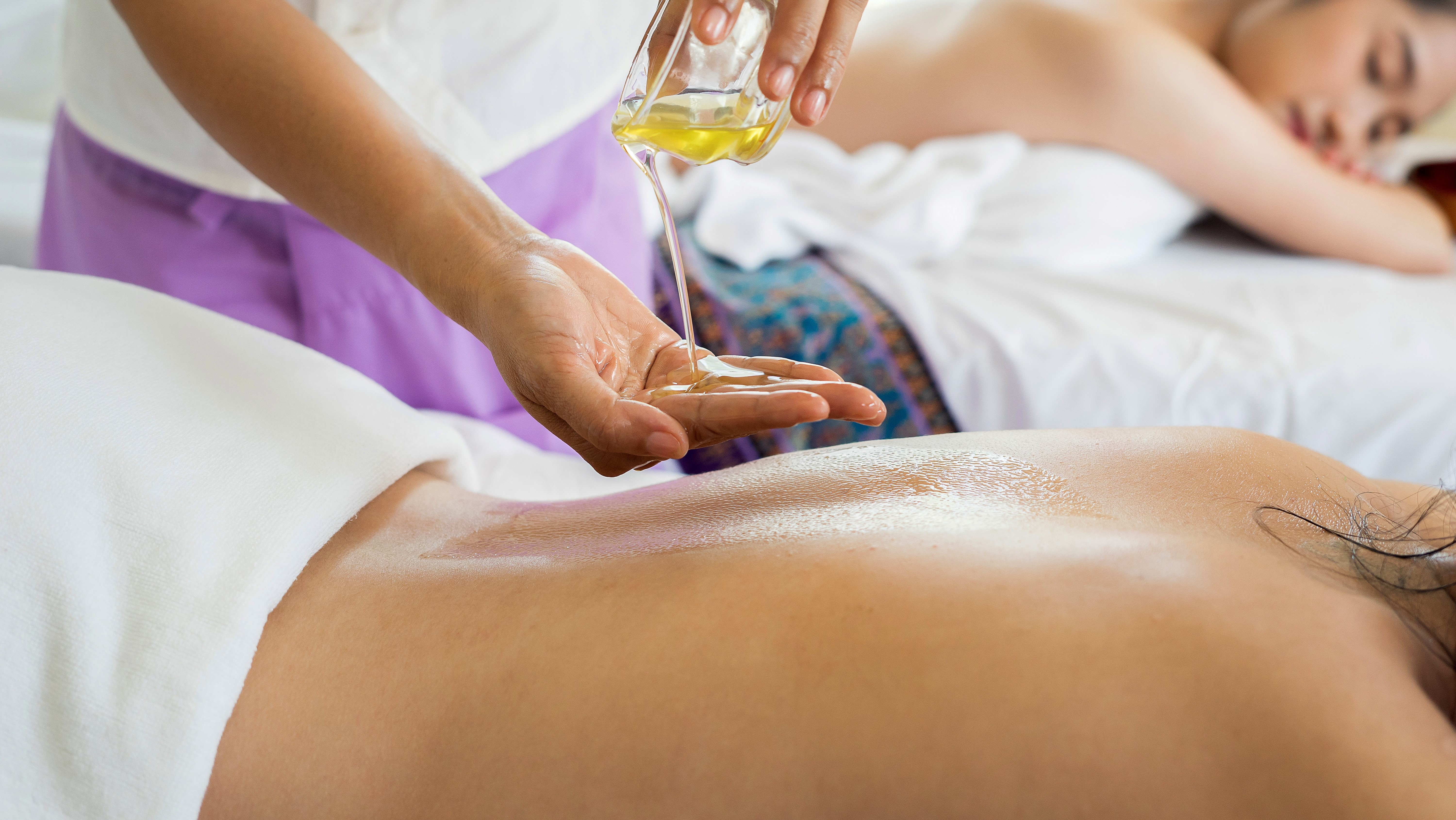 person getting massaged with oil at the spa