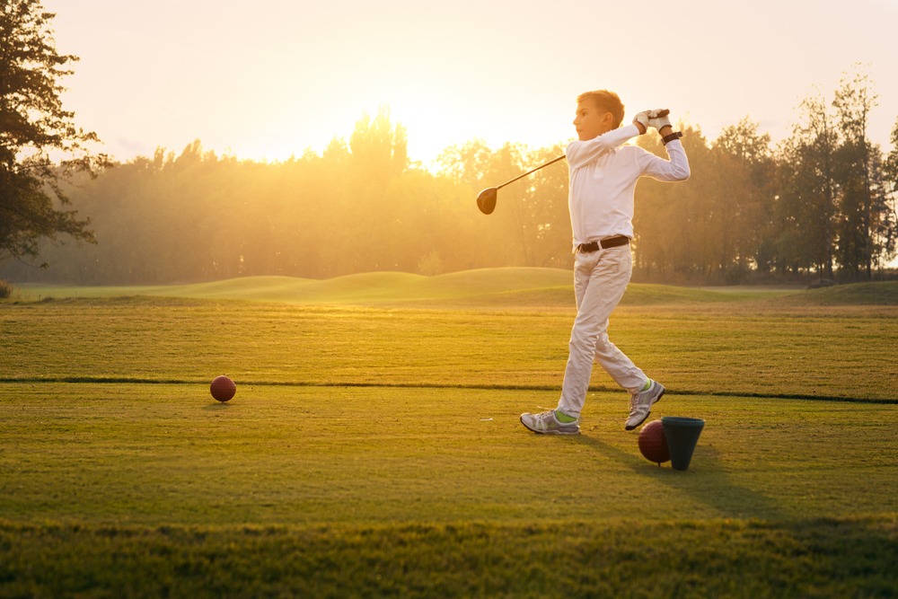 young golfer hitting a ball