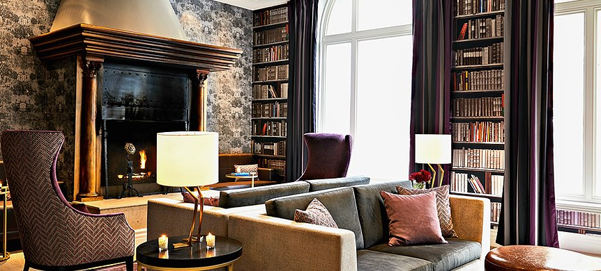 Living space with black marble fireplace and library next to windows