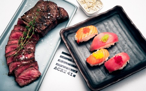 sliced steak and a tray of sushi