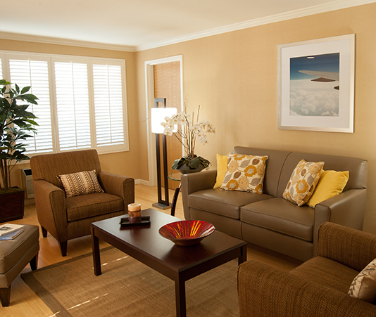 Double Suite room with seating area contains couch, coffee table, several single chairs, lamp adjacent to window