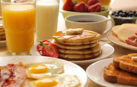 breakfast spread of pancakes, eggs, bacon, toast, OJ