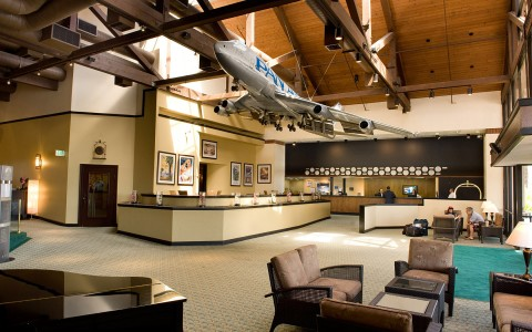 hotel lobby, enter directly to front desk which features large aircraft hanging from ceiling. Seating area off to left