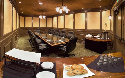 Meeting and conference at Airtel room contains 1 long board room style table with several large leather desk chairs and 2 tables set up for refreshments