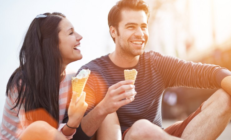 attractive young couple eating ice cream and laughing