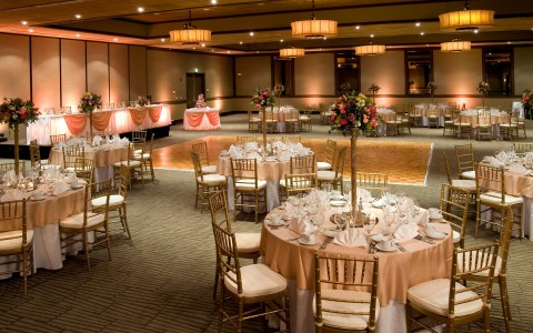 Airtel wedding reception circular tables draped in pink and white linen and fine table ware and dance floor in the middle