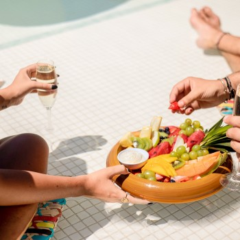guests eating out of floating dish with fruit