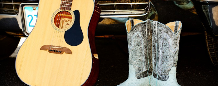 Acoustic wood panelled guitar by a cadillac and cowboy boots