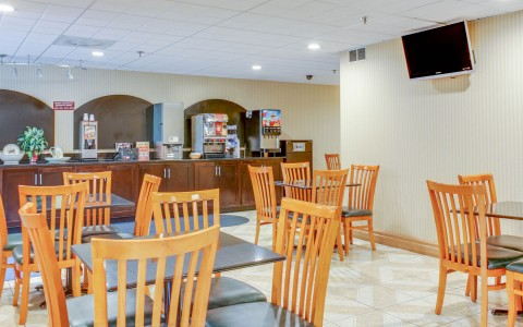 Dining area with square tables, wooden chairs & counter with breakfast items