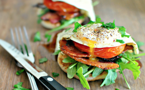 Eggs Benedict on top of spinach, tomato & bacon