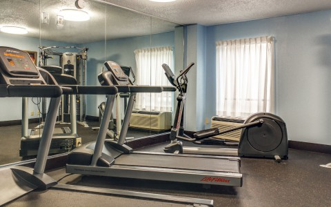 Fitness room with cardio machines in front of mirror