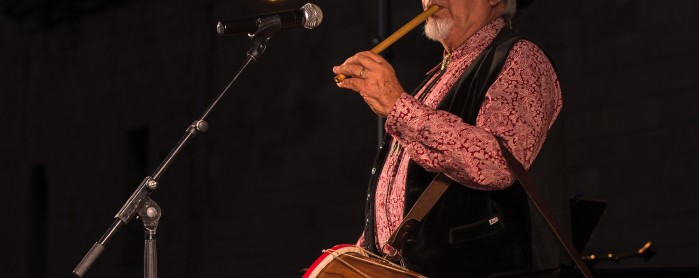 Old man with fife and boat performing at microphone