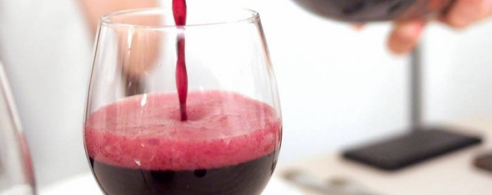 Red wine being poured into a wine glass on a wooden table