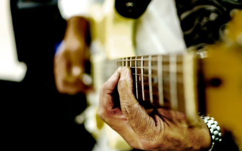 Close up of a man's hands playing guitars