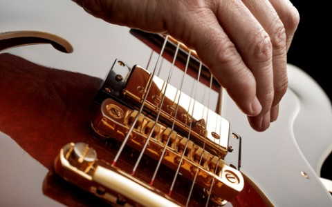 Close up of hand strumming electric guitar