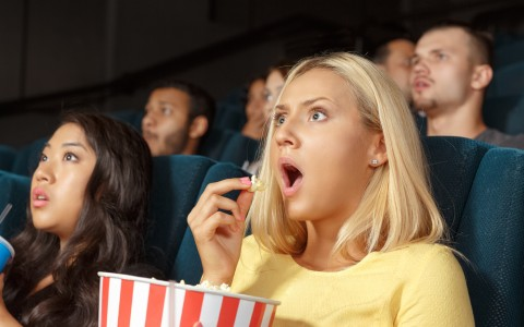 People in movie theater with surprised looks on their faces
