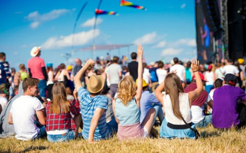 Crowd of of people sitting on grass enjoying daytime concert