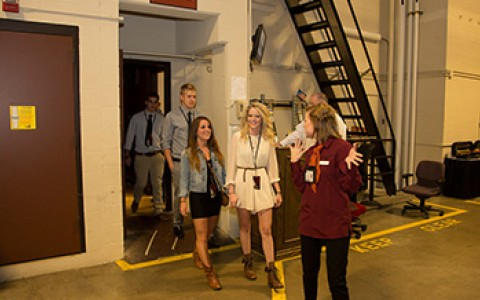 Group of young adults getting toured backstage