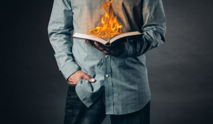 man reading a book on fire