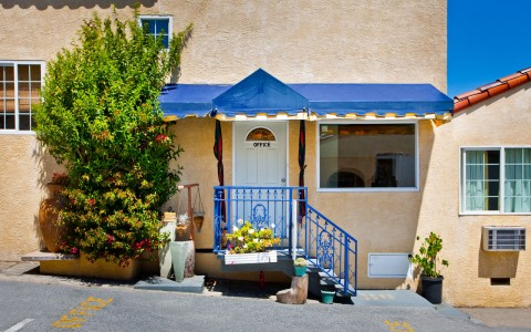 Entry from outside. Front door of unit. 3 small stairs with royal blue railing and awning