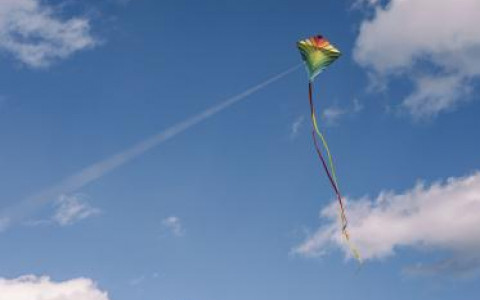 Colorful Kite Flying in a blue sky with white fluffy clouds