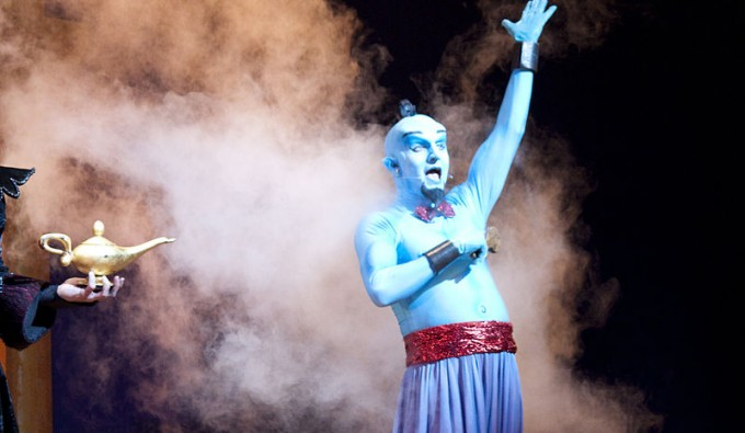 Genie from Aladdin on stage surrounded by smoke