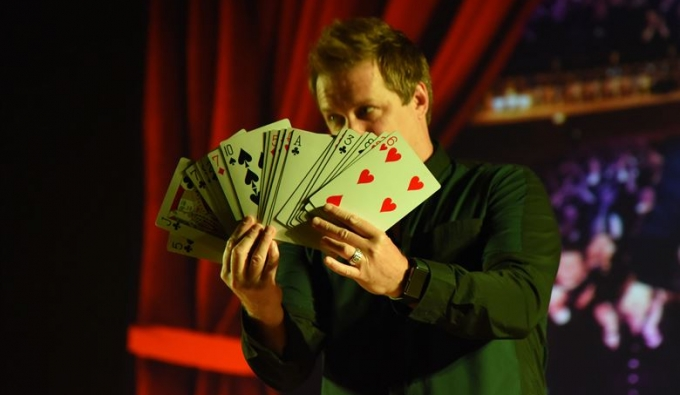 Magician with large cards for a trick