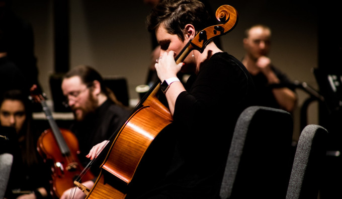 concert cellist wearing black while playing in a symphony