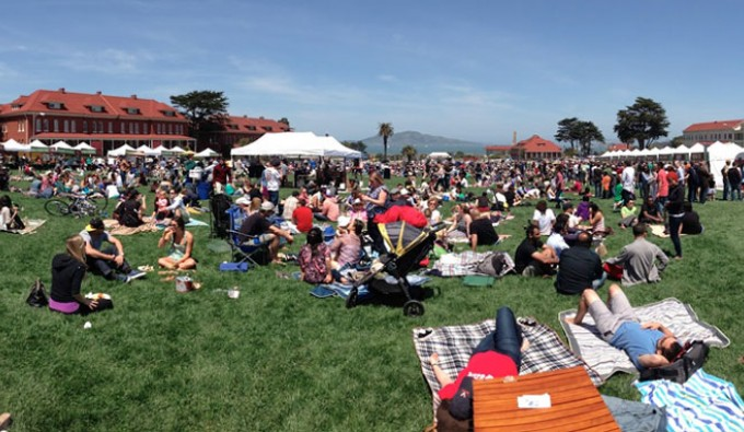 picnic at the presidio. 100's of people set up picnic blankets and tents on a open lawn.
