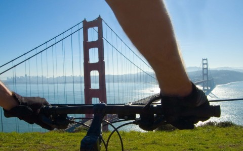 person on bike atop a cliff in front of golden gate bridge