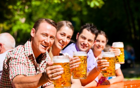 group of friends cheersing beer at camera