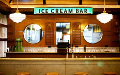 retro ice cream bar with stools up to a bar. glass cups line the back wall with a door into the kitchen.