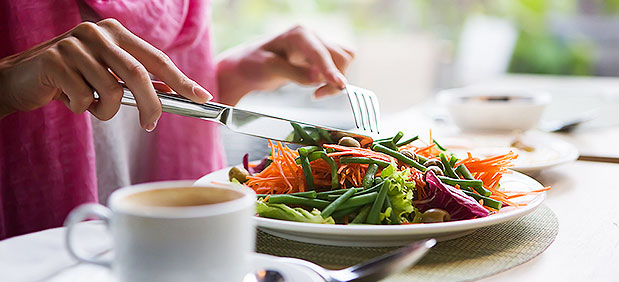 person preparing to eat salad at white cloth table