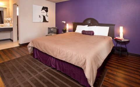 In room image of large bed with tan duvet and multi colored purple and tan walls. Accent photo of Audrey Hepurn. Double night stands and water closet style bathroom