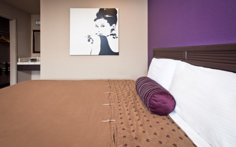 In room image of large bed with tan duvet and multi colored purple and tan walls. Accent photo of Audrey Hepurn