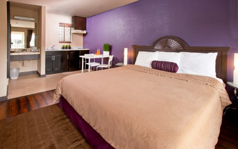 King sized bed in room with kitchenette and vibrant purple walls