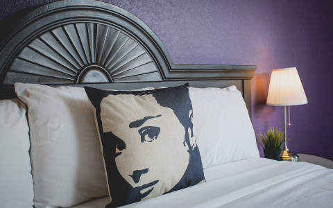 alura interior room image showing queen bed with audrey hepburn pillow