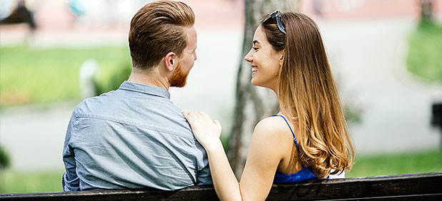 man and women sitting on park bench. Womens hand on mans shoulder