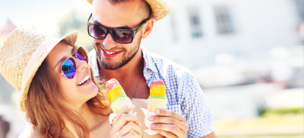 Cheerful couple wearing hats and sunglasses holding ice cream cones