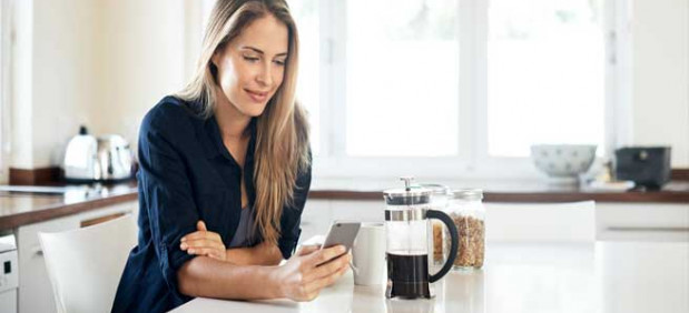 Young woman on her phone while enjoying a cup of coffee