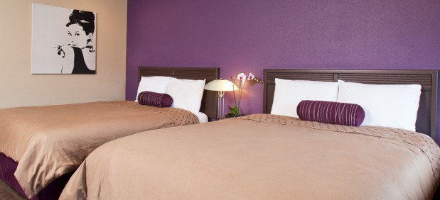 2 double beds with tan duvet and purple walls. Signature Audrey Hepburn painting on the wall