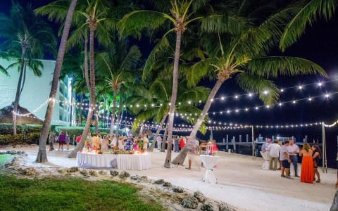 Wedding venue at night with tables set up and lights on palm trees