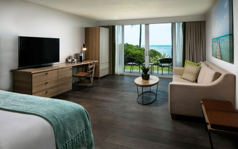 Room with queen bed and sofa with view of the ocean
