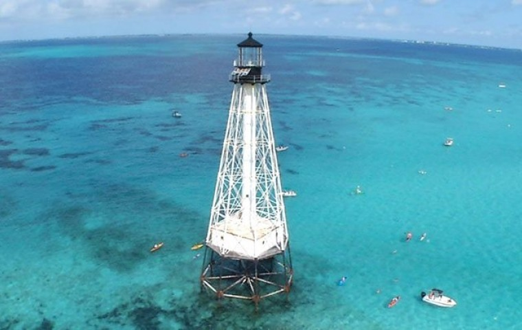 lighthouse in the middle of ocean with scuba divers around