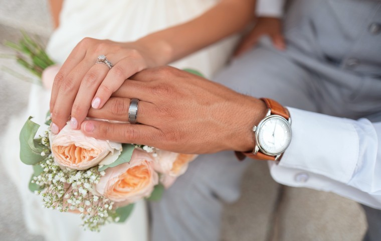 man and wife holding hands over a bouquet of flowers