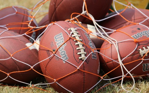 American footballs under orange and white netting