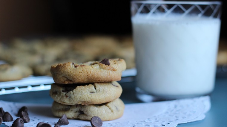 Close up on glass of milk and stack of chocolate chip cookies on doily