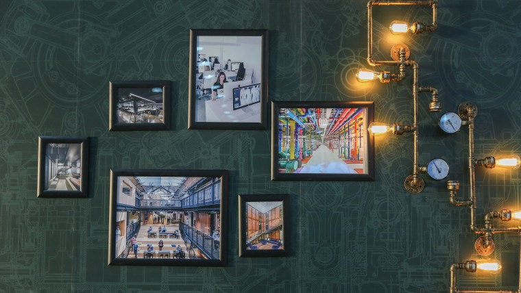 Exhibition of photographs of modern interiors against a dark green wall with steampunk lighting apparatus