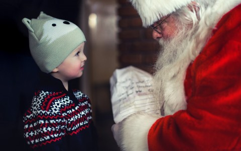 Santa holding list in front of small boy in Christmas sweater and knit cap